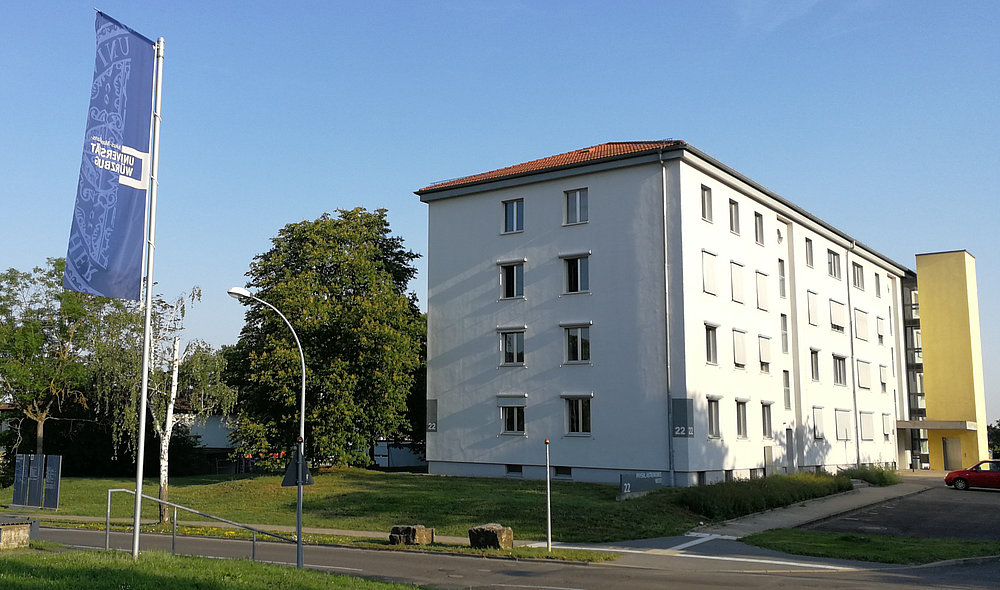 from left white-blue banner of the Würzburg University, white building with yellow advancing stone wall of the lift.