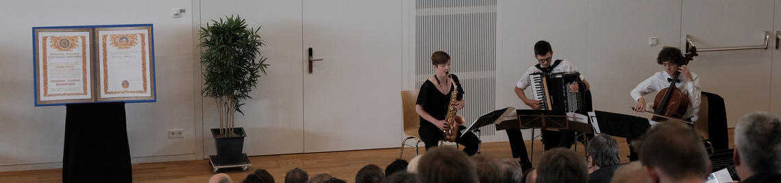 3 musicians on the stage of the lecture hall
